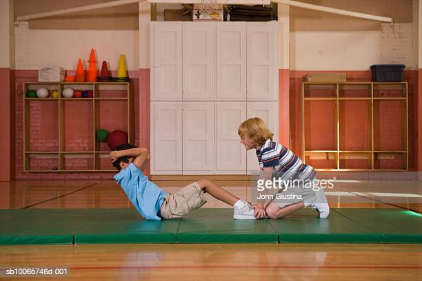 Two boys (7-9) exercising in school gymnasium, side view