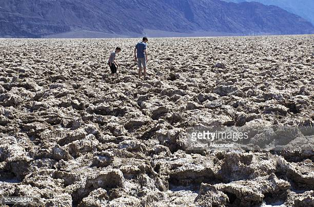 Two boys explore the Devil's Golf Course a popular attraction in Death Valley National Park in California on March 29 2016 The area's large salt...