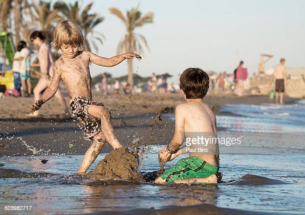 Two boys fighting in mud and water