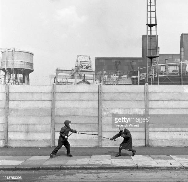 Two boys fighting with sticks in front of a concrete wall London UK circa 1960