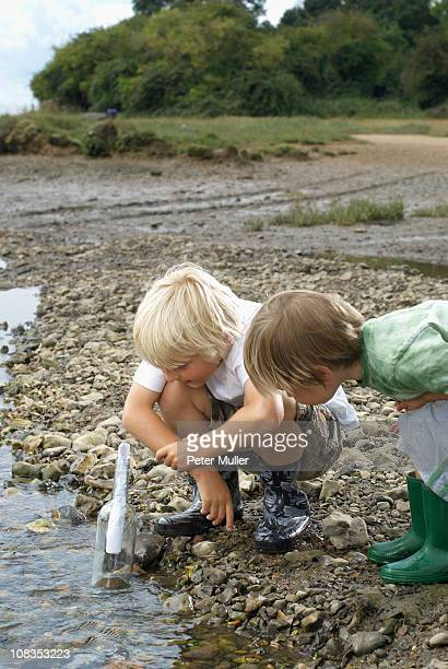 Two boys finding a message in a bottle