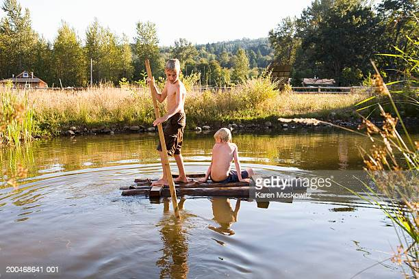 Two boys (7-9) floating on wooden raft in pond