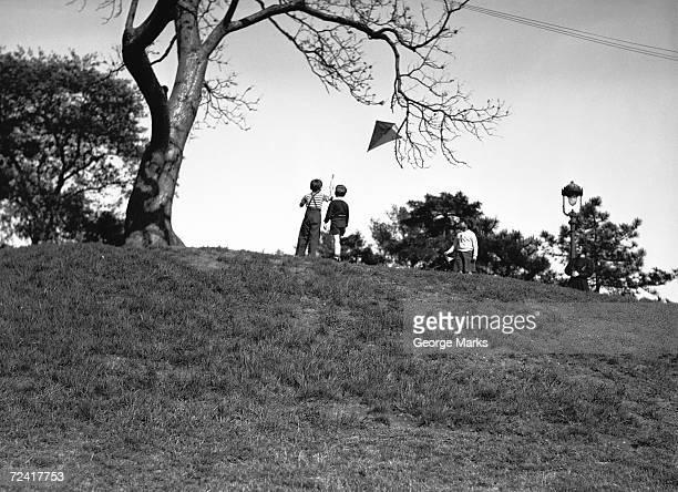 Zwei Jungen (10-11) fliegen kite am hill (Rückansicht), (B & W