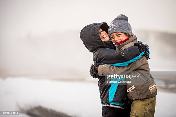 two boys. Friends. Big hug. Snow. Winter