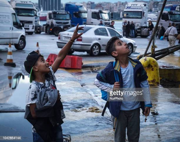 Two boys from Syria look a ferry following disembark at the Port Piraeus 29 September 2018 Thousand migrants and refugees are scheduled to arrive at...