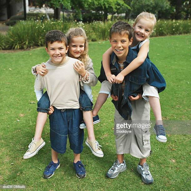 Two boys (10-12) give two girls (8-9) a piggyback