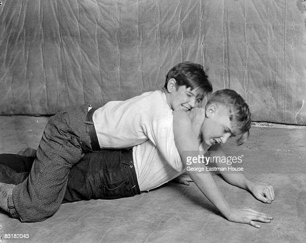 Two boys grapple with each other as they wrestle on the ground United States ca1920s