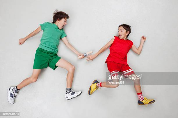 two boys handing over baton at relay race - relay stock pictures, royalty-free photos & images