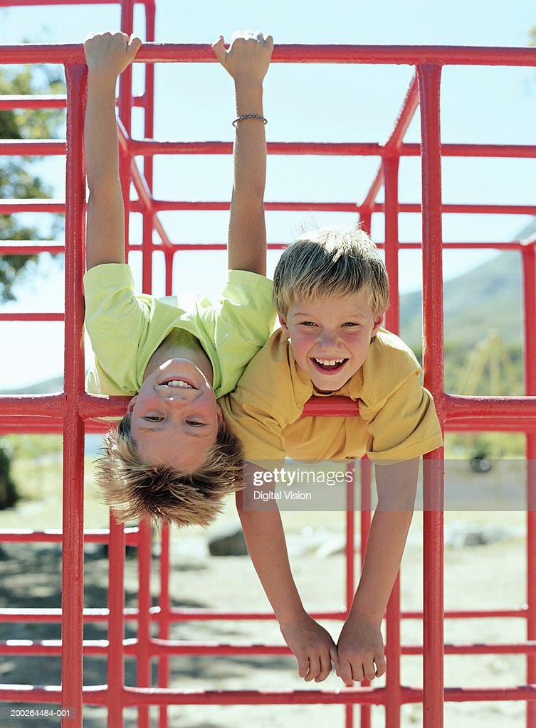 Two boys (9-11) hanging on bars in playground, smiling, portrait : Stock Photo