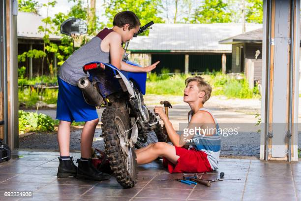Two boys hanging out and working on a dirt bike.
