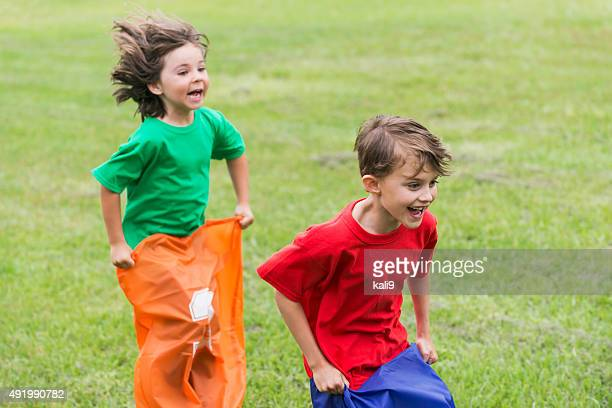 Two boys having fun competing in potato sack race