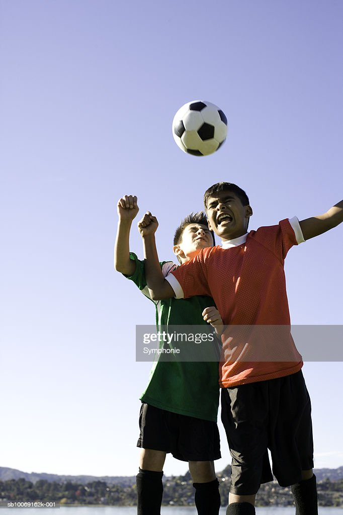 Two boys heading football, eyes closed : Stockfoto