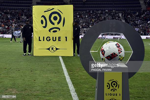 Two boys hold a banner with the official Ligue 1 logo in front of the official ball prior to the French L1 football match between Toulouse and...