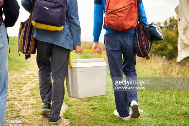 two boys holding a cool box walking to a camping spot - friendship stock pictures, royalty-free photos & images