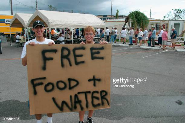 Two boys holding a free food and water sign at Port Charlotte after Hurricane Charley damage