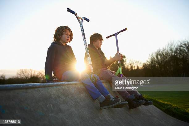 Two boys holding micro scooters sitting on ramp.