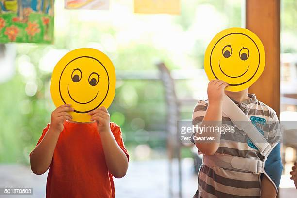 Two boys holding up smiley face masks at nursery school