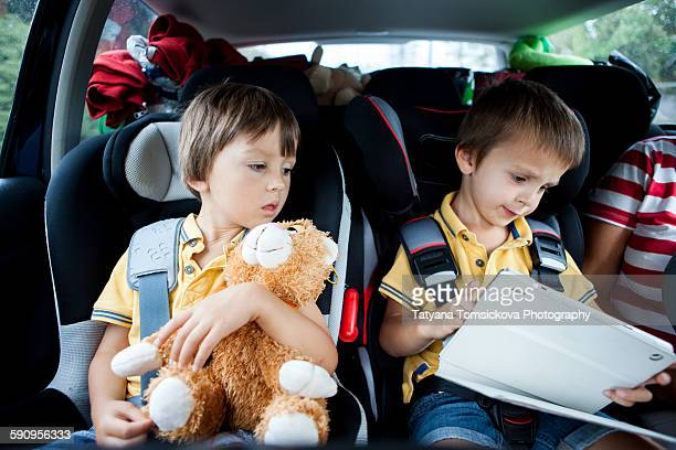 Two boys in car, one playing on tablet