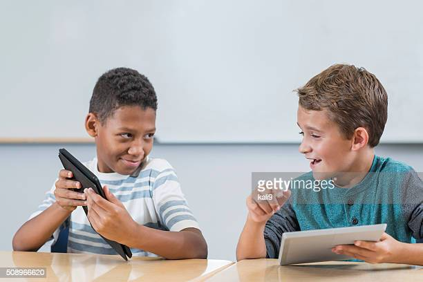 Two boys in class with digital tablets