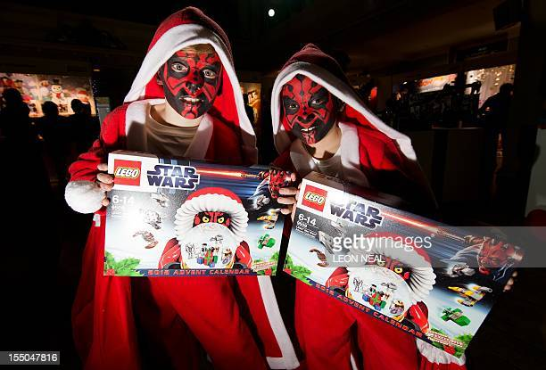 Two boys in festive costumes with their faces painted like the Star Wars character Darth Maul pose with the Lego Star Wars advent gift calendar at...