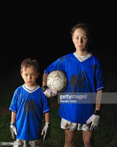 Two boys (5-11) in football outfits, older boy holding ball, portrait