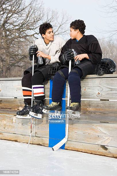 two boys in hockey uniforms sitting on ice rink wall - ice hockey uniform stock pictures, royalty-free photos & images
