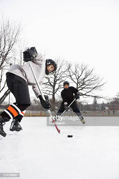 two boys in ice hockey uniforms skating on ice rink moving puck. - ice hockey uniform stock pictures, royalty-free photos & images