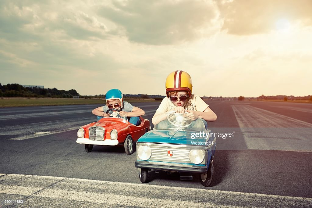 Two boys in pedal cars crossing finishing line on race track : Stock Photo