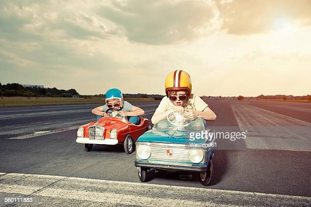 two boys in pedal cars crossing finishing line on race track - competizione foto e immagini stock