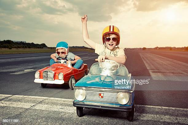 two boys in pedal cars crossing finishing line on race track - cool cars stock pictures, royalty-free photos & images