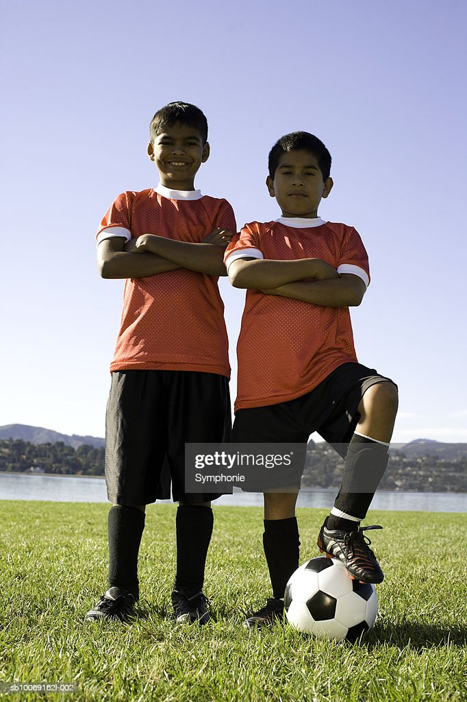 Two boys in soccer uniform standing with ball, portrait : Stockfoto