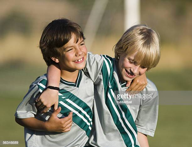 Two boys in soccer uniforms, with arms around each other