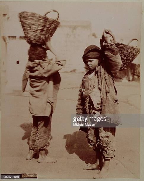 Two boys in torn and threadbare pans and jackets carry baskets on their head. Naples, Italy, 1880s-1890s.