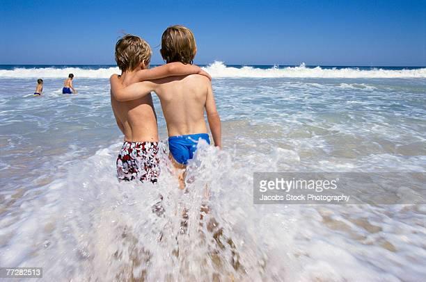 Two boys in water hugging