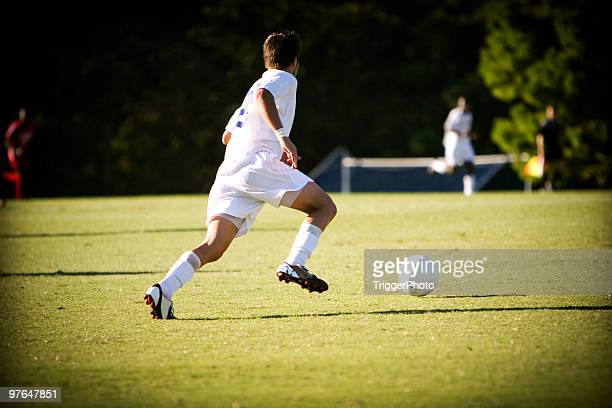 two boys in white outfits playing soccer in the field - rush fútbol americano stock photos and pictures
