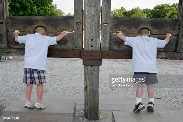 Two boys in wood frame stocks on Duke of Glouster Street