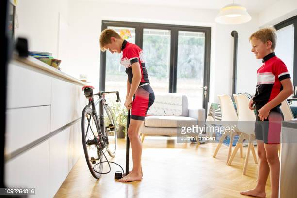 two boys inflating their tyres preparing their bike ready for a bike ride - inflating stock pictures, royalty-free photos & images