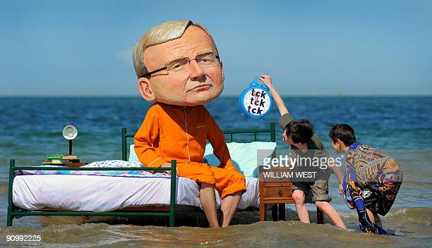 Two boys inspect a man wearing a caricature head of Australian Prime Minister Kevin Rudd in pyjamas while sitting on a bed at St Kilda beach in...