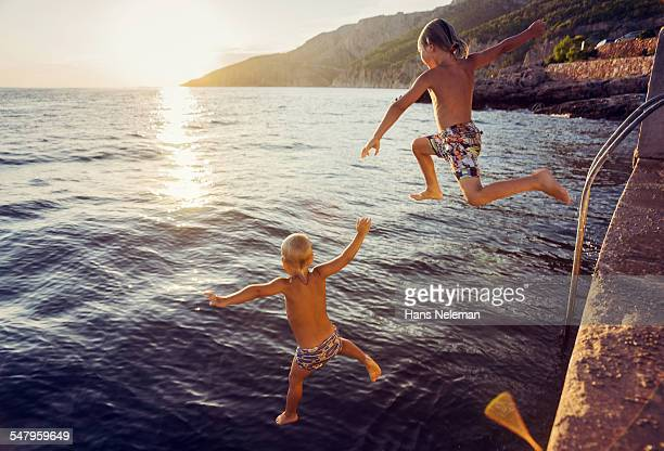 Two boys jumping into sea