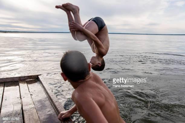 two boys jumping into water - jungen in badehose 12 jahre stock-fotos und bilder