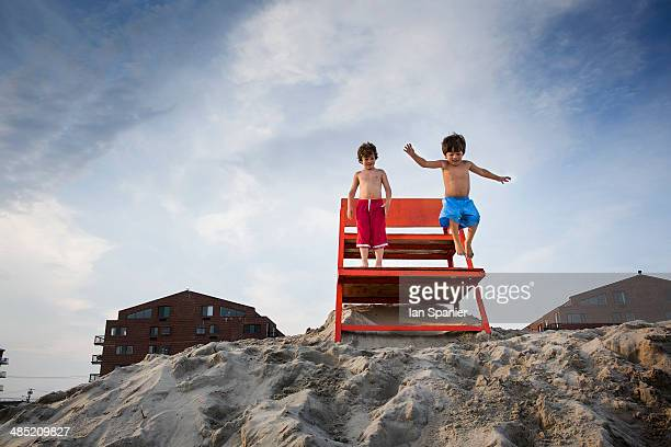 Two boys jumping off red notice board, Long Beach, New York State, USA