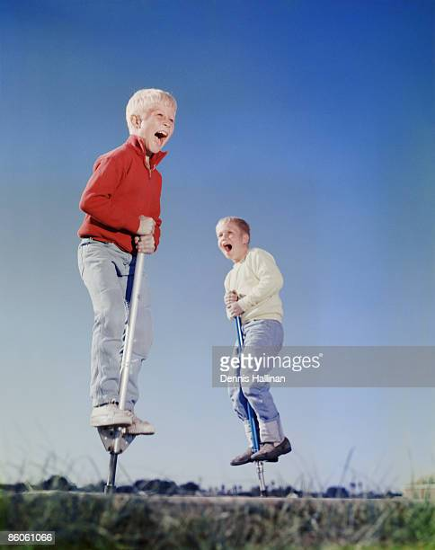 Two Boys Jumping on Pogo Sticks