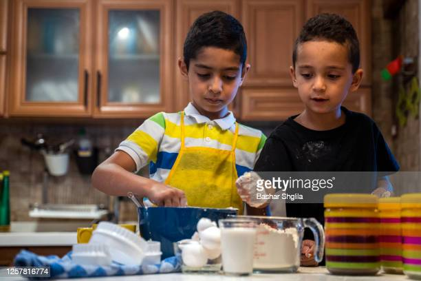 two boys learn to bake in the kitchen at home - north africa stock pictures, royalty-free photos & images