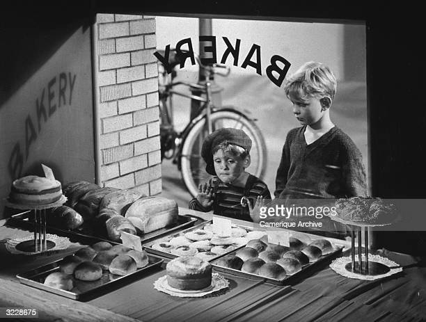 Two boys look into the window of a bakery eyeing trays of freshly baked muffins pastries and loaves of bread The younger boy has his nose and hands...