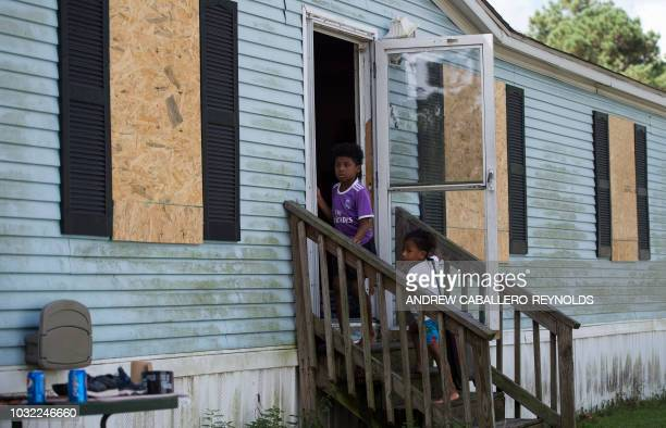 Two boys look on as they enter their mobile home a day before the arrival of Hurricane Florence in Wilmington, North Carolina on September 12, 2018....