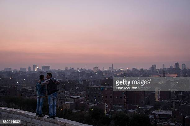 Two boys look out over the Cairo skyline at sunset on December 10 2016 in Cairo Egypt Since the 2011 Arab Spring Egyptians have been facing a crisis...