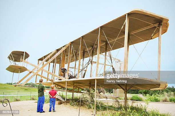 Two boys looking at a sculpture of the Wright Brothers airplane. Wright Brothers First Flight Centennial Memorial, Wright Brothers National Memorial,...