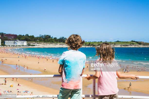 Two boys looking at El Sardinero beach, Santander, Cantabria, Spain