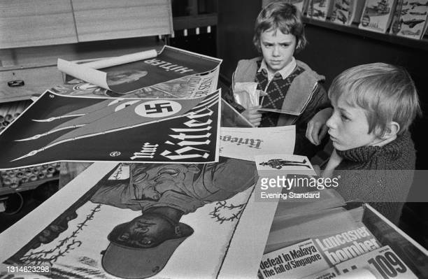 Two boys looking at German propaganda from World War II at the Imperial War Museum in London, UK, 26th March 1974. The top poster is an election...