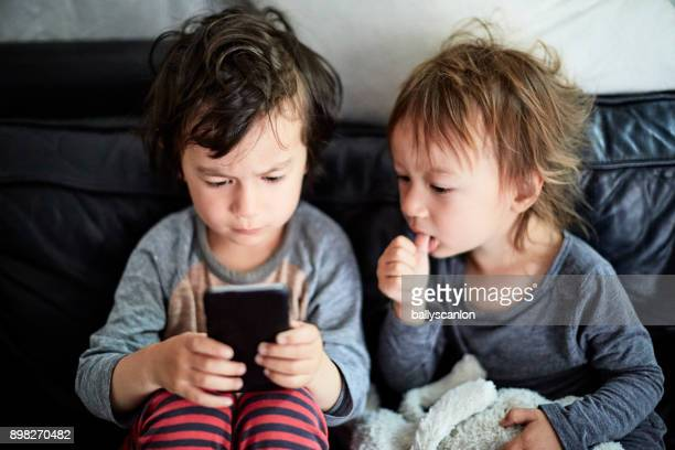 Two Boys Looking At Mobile Phone